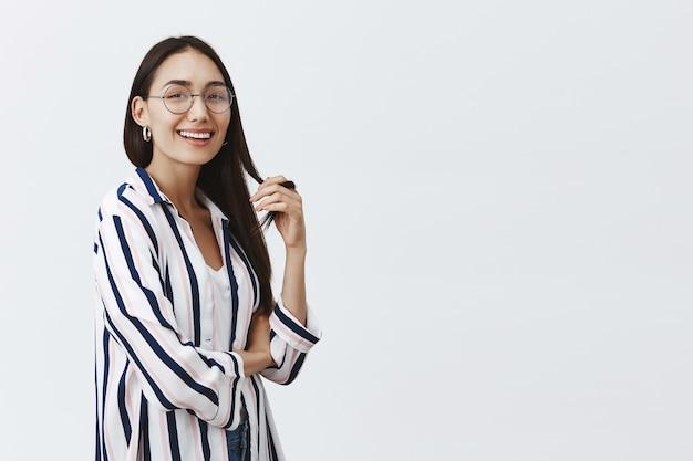 Portrait de jolie femme insouciante et heureuse à lunettes et chemisier rayé, jouant avec une mèche de cheveux et souriant largement avec confiance
