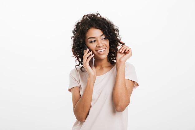 Portrait de jolie femme joyeuse avec une coiffure à la mode portant un t-shirt de base parler au téléphone mobile et toucher ses serrures marron, isolé sur un mur blanc