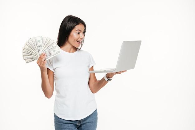 Portrait d'une jolie femme joyeuse tenant un ordinateur portable