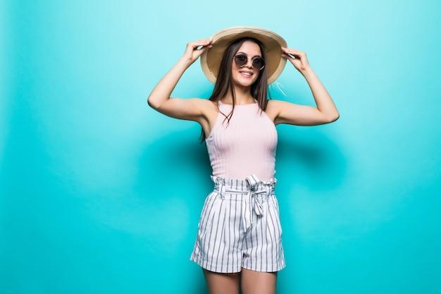 Portrait de jolie femme à lunettes de soleil et chapeau sur bleu coloré. concept d'été.