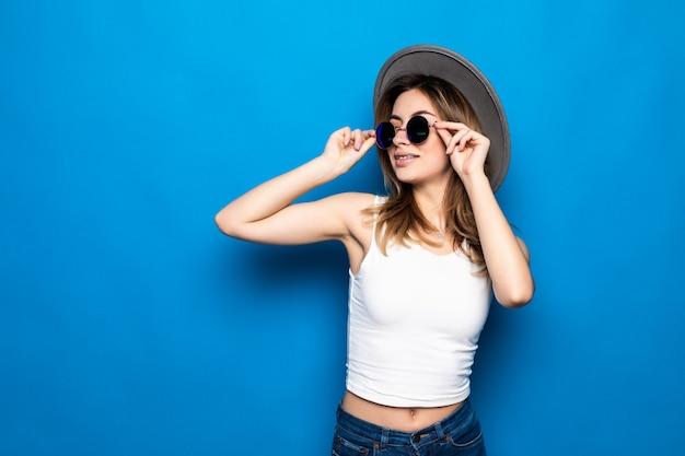 Portrait de jolie femme à lunettes de soleil et chapeau sur mur coloré bleu