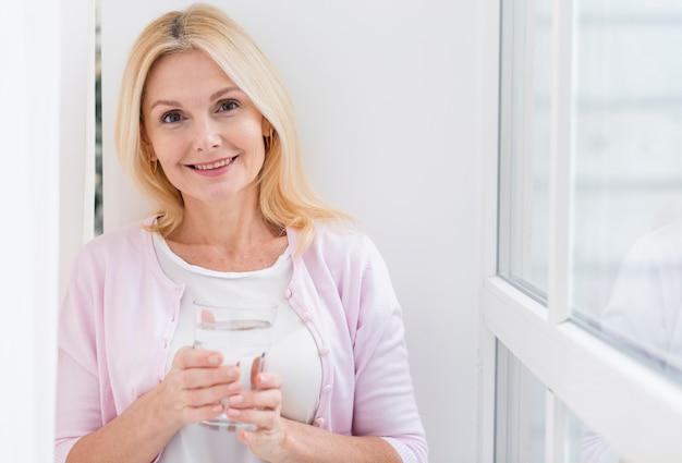 Portrait de jolie femme mature tenant un verre d'eau