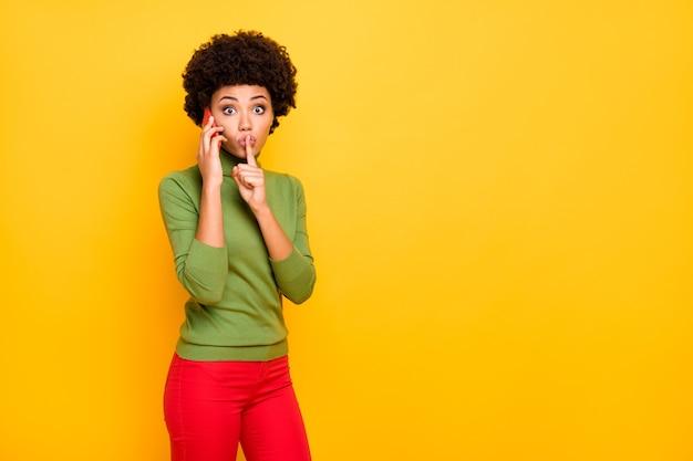 Portrait de jolie femme mignonne vous montrant chut signe avec l'index touchant les lèvres dans un pantalon rouge près d'un espace vide parlant au téléphone cheveux bruns ondulés bouclés.