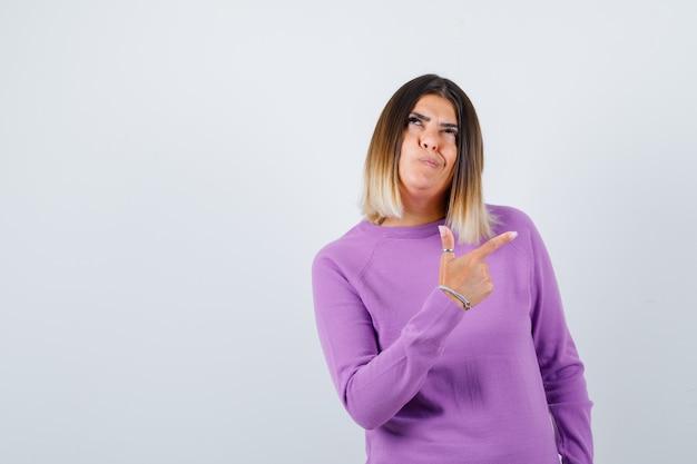 Portrait de jolie femme pointant vers le coin supérieur droit, levant les yeux dans un pull violet et regardant la vue de face pensive