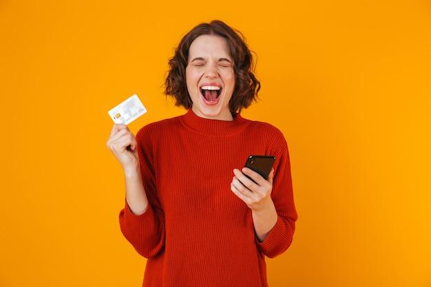 Portrait de jolie femme portant un pull à l'aide de téléphone portable et carte de crédit en position debout isolé sur jaune