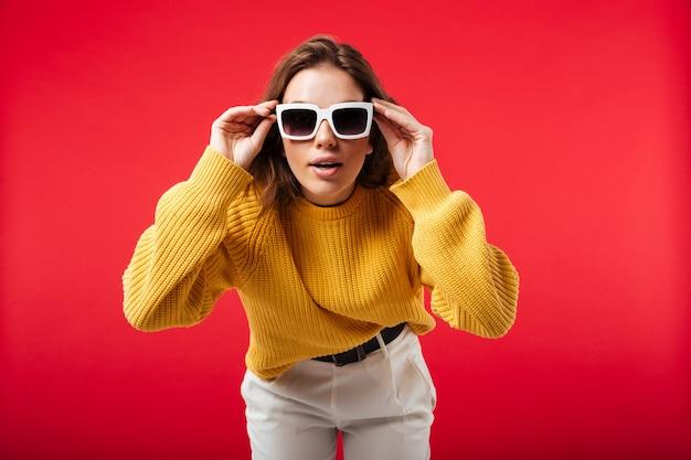 Portrait d'une jolie femme en posant des lunettes de soleil