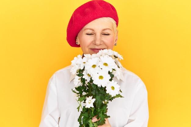 Portrait de jolie femme de race blanche mature aux cheveux blonds célébrant la journée internationale de la femme, recevant des marguerites blanches de son fils, souriant joyeusement