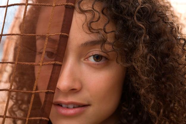 Portrait de jolie femme regardant à travers un drapé translucide