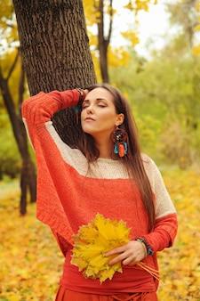 Portrait de jolie femme relaxante les yeux fermés dans le parc d'automne