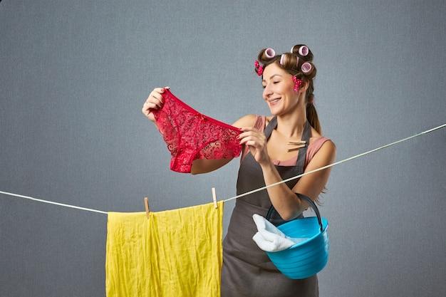 Portrait d'une jolie femme rétro accrocher des culottes dans une ficelle sur un mur gris. fanny femme au foyer portant des bigoudis séchant des vêtements. concept de ménage.