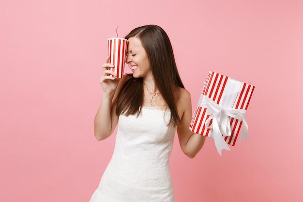 Portrait d'une jolie femme riante en robe blanche tenant une boîte rouge avec un cadeau, présente une tasse en plastique avec du cola ou du soda