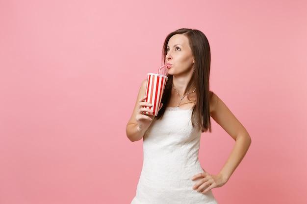 Portrait de jolie femme en robe blanche debout, regardant de côté et buvant du cola ou du soda dans une tasse en plastique