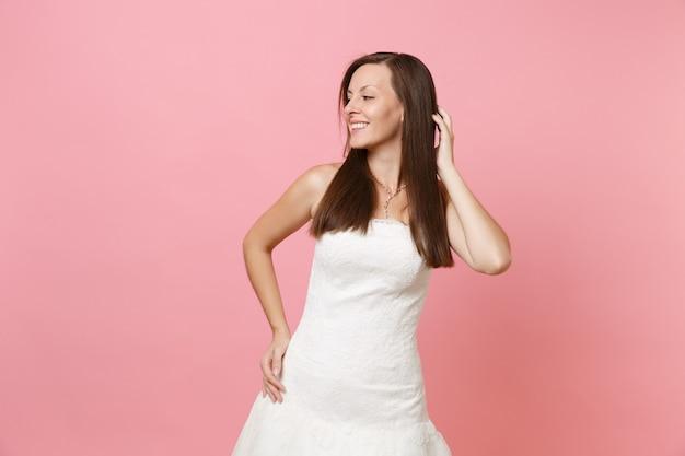 Portrait de jolie femme en robe blanche élégante debout regardant de côté en gardant la main sur les cheveux