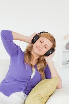 Portrait d'une jolie femme rousse écoutant de la musique et appréciant le moment tout en étant assis sur un canapé