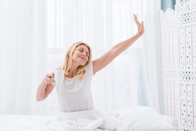 Portrait de jolie femme se réveillant avec du café