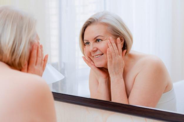 Portrait jolie femme senior avec les mains sur son miroir de visage à la maison après la salle de bain soins de la peau après 50-60 ans