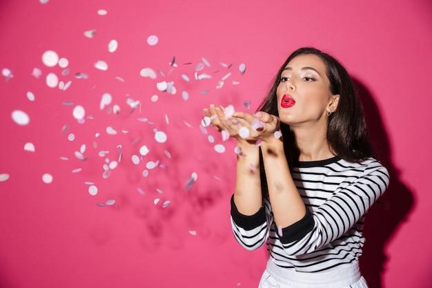 Portrait d'une jolie femme soufflant des confettis