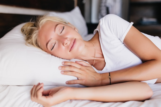Portrait de jolie femme souriant doucement pendant son sommeil. photo intérieure d'un mannequin rêveur portant un bracelet.