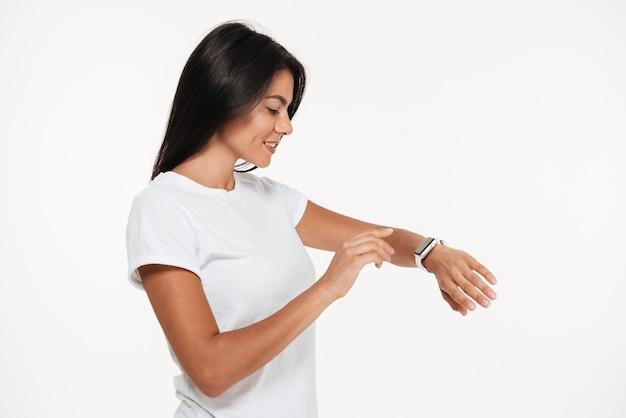 Portrait d'une jolie femme souriante à l'aide de la montre intelligente