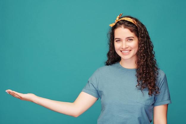 Portrait de jolie femme souriante aux cheveux bouclés pointant de côté tout en recommandant le produit sur bleu