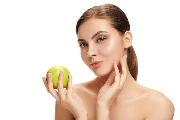 Le portrait de jolie femme souriante caucasienne isolée sur fond de studio blanc avec des fruits de pomme verte. le concept de beauté, soins, peau, traitement, santé, spa, cosmétique et publicité