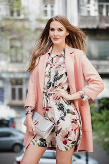 Portrait de jolie femme souriante élégante marche rue de la ville en manteau rose et robe à fleurs