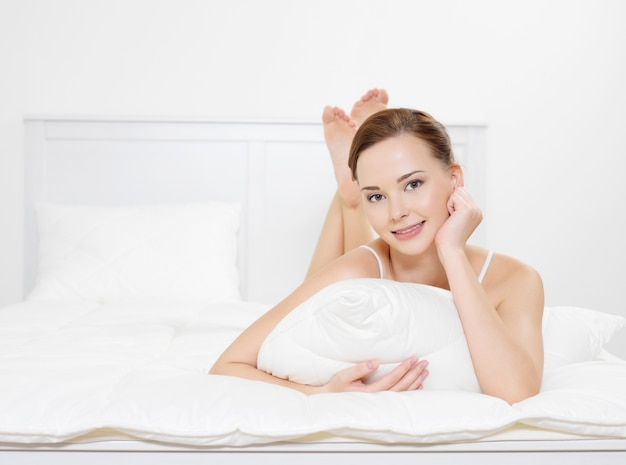 Portrait de la jolie femme souriante se détend allongé sur le lit