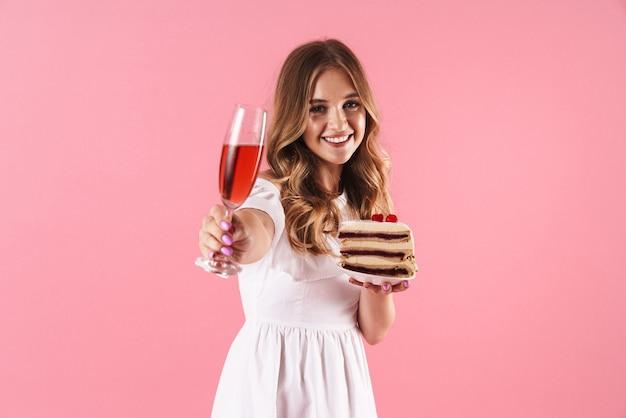 Portrait d'une jolie femme souriante vêtue d'une robe blanche tenant un morceau de gâteau et un verre de vin isolé sur un mur rose