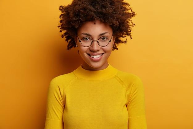 Portrait de jolie femme sourit doucement, a les cheveux bouclés, porte des lunettes rondes transparentes et un pull jaune, regarde directement, écoute des nouvelles agréables, pose à l'intérieur. expressions de visage humain
