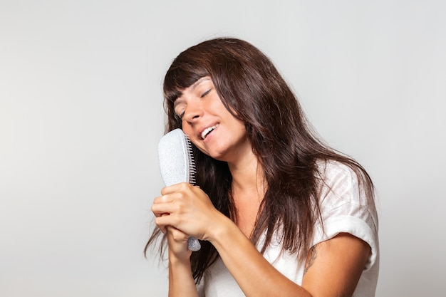 Portrait d'une jolie femme tatouée, chantant dans une brosse à cheveux comme dans un micro, fermant les yeux. fond blanc. le concept de soins capillaires et de plaisir.