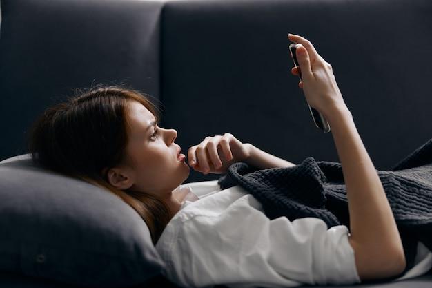 Portrait de jolie femme avec téléphone portable sur le canapé vue recadrée.