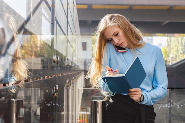 Portrait de jolie femme avec un téléphone portable dans la rue
