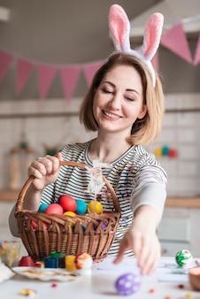 Portrait de jolie femme tenant un panier avec des oeufs de pâques