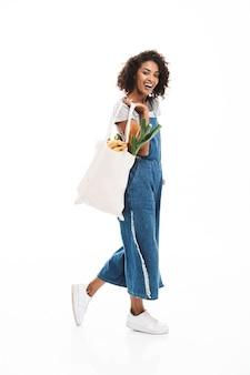 Portrait d'une jolie femme tenant un sac en coton avec des produits alimentaires et marchant isolée sur un mur blanc