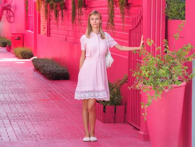 Portrait d'une jolie femme touriste vêtue d'une robe rose