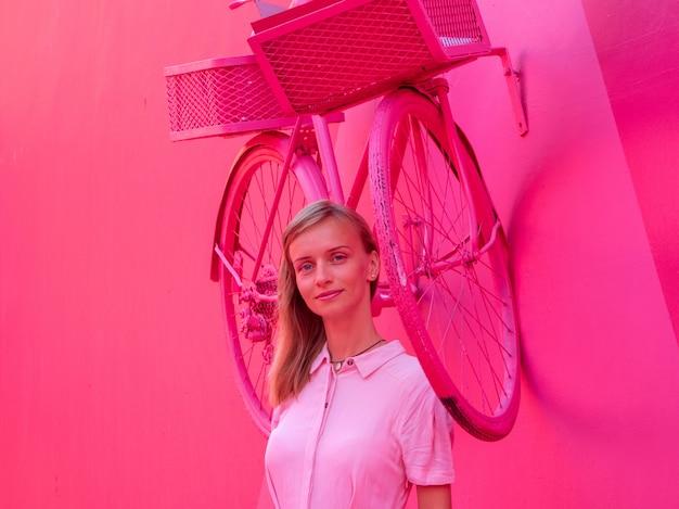 Portrait d'une jolie femme vêtue d'une robe rose sur un alle rose