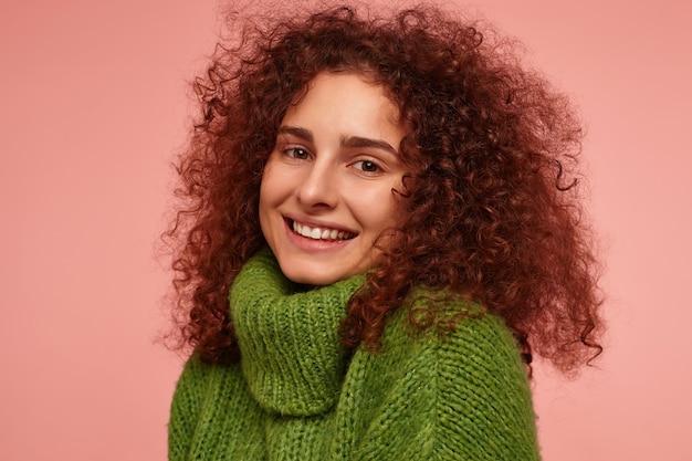 Portrait de jolie fille adulte aux cheveux bouclés roux. vêtu d'un pull à col roulé vert et souriant. regarder flirty isolé, gros plan sur un mur rose pastel