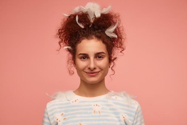 Portrait de jolie fille adulte aux cheveux bouclés roux. vêtu d'un pull rayé avec des lapins et couvert de plumes, souriant. isolé, gros plan sur un mur rose pastel