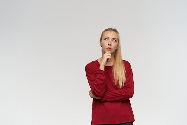 Portrait de jolie fille adulte aux cheveux longs blonds. porter un pull rouge. concept de personnes et d'émotion. regarder attentivement à copie espace, isolé sur fond blanc