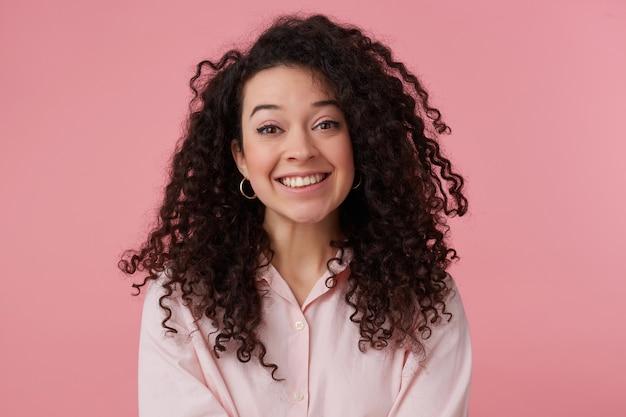 Portrait de jolie fille adulte aux longs cheveux bouclés foncés. porter des boucles d'oreilles et une chemise rose pastel. a du maquillage. souriant largement