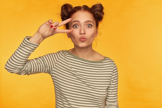 Portrait de jolie fille adulte avec deux petits pains et de grands yeux. portant un chemisier à rayures et montrant un signe de paix sur son œil, baiser isolé sur mur jaune