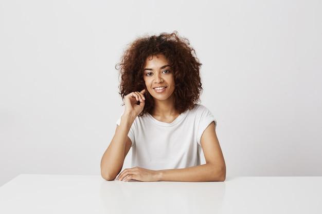 Portrait de jolie fille africaine souriant sur mur blanc