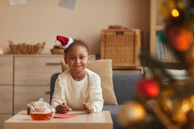 Portrait de jolie fille afro-américaine écrit une lettre au père noël alors qu'il était assis à table par arbre de noël, copiez l'espace