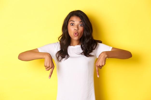 Portrait de jolie fille afro-américaine pointant les doigts vers le bas et l'air étonné