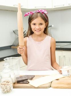 Portrait de jolie fille apprenant la cuisine dans la cuisine à la maison
