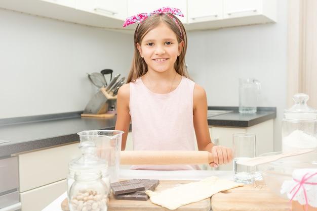 Portrait de jolie fille apprenant la cuisine dans la cuisine
