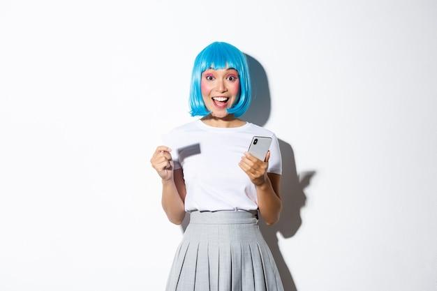 Portrait de jolie fille asiatique déguisée en personnage d'anime en perruque bleue, tenant une carte de crédit et un téléphone mobile