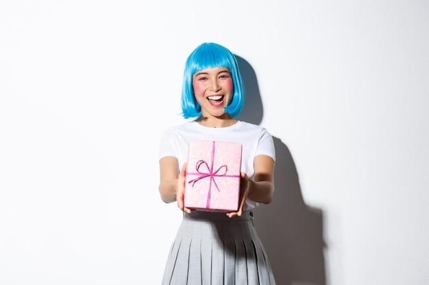 Portrait de jolie fille asiatique heureuse en perruque de fête bleue vous donnant un cadeau, debout.