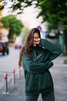 Portrait de jolie fille aux cheveux longs regarde la caméra en ville sur fond de rue.