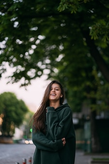 Portrait de jolie fille aux cheveux longs regarde la caméra en ville sur rue